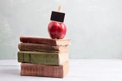 Apple σε έναν σωρό των βιβλίων στον πίνακα Στοκ Φωτογραφία