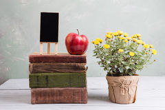 Apple σε έναν σωρό των βιβλίων στον πίνακα Στοκ Εικόνες