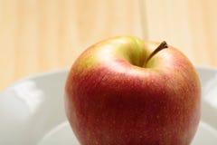 Apple σε ένα άσπρο πιάτο Στοκ φωτογραφία με δικαίωμα ελεύθερης χρήσης
