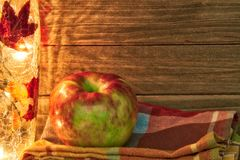 Apple σε ένα θέμα πτώσης με το φως και την πετσέτα και ένα ξύλινο υπόβαθρο που παρέχει το διάστημα αντιγράφων Στοκ φωτογραφία με δικαίωμα ελεύθερης χρήσης
