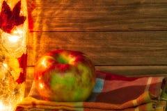 Apple σε ένα θέμα πτώσης με το φως και την πετσέτα και ένα ξύλινο υπόβαθρο που παρέχει το διάστημα αντιγράφων Στοκ Εικόνα