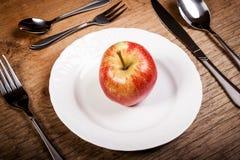 Apple σε ένα πιάτο με τα μαχαιροπήρουνα σε έναν παλαιό ξύλινο πίνακα Στοκ φωτογραφίες με δικαίωμα ελεύθερης χρήσης