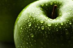Apple σε πράσινο με τις πτώσεις νερού στην επιφάνειά του Στοκ Εικόνες