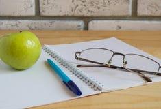 Apple, σημειωματάριο, διαβάζοντας τα γυαλιά και τη μάνδρα στον ξύλινο πίνακα πίσω σχολείο έννοιας Στοκ εικόνα με δικαίωμα ελεύθερης χρήσης