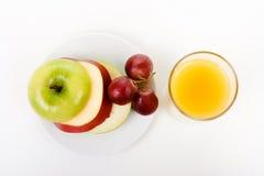 Apple, σταφύλια σε ένα πιάτο και ένα ποτήρι του χυμού από πορτοκάλι Στοκ Φωτογραφία
