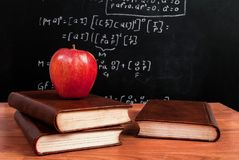 Apple στα βιβλία σε ένα ξύλινο γραφείο κατά τη διάρκεια της κατηγορίας math στην τάξη Στοκ Φωτογραφίες