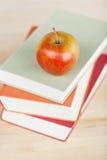 Apple στα συσσωρευμένα βιβλία στον πίνακα Στοκ Εικόνες