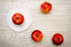 Apple στα ώριμα μήλα πιατακιών σε ένα ελαφρύ ξύλινο υπόβαθρο Στοκ φωτογραφία με δικαίωμα ελεύθερης χρήσης