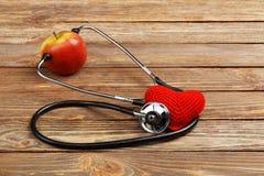 Apple, στηθοσκόπιο και καρδιά στο ξύλινο υπόβαθρο Στοκ φωτογραφία με δικαίωμα ελεύθερης χρήσης
