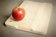 Apple στον ξύλινο τέμνοντα πίνακα Στοκ φωτογραφία με δικαίωμα ελεύθερης χρήσης