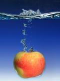 Apple στον παφλασμό νερού πέρα από το μπλε υπόβαθρο Στοκ Φωτογραφίες