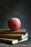 Apple στο βιβλίο και το μαύρο υπόβαθρο Στοκ φωτογραφία με δικαίωμα ελεύθερης χρήσης