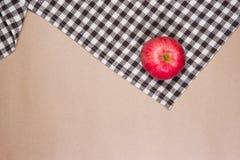 Apple στο καφετί επιτραπέζιο ριγωτό ύφασμα και το υπόβαθρο καφετιού εγγράφου Στοκ Εικόνες