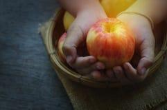 Apple στο καλάθι και το χέρι Στοκ Εικόνες