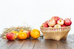 Apple στο καλάθι μπαμπού και πορτοκάλια στον ξύλινο πίνακα Στοκ φωτογραφία με δικαίωμα ελεύθερης χρήσης