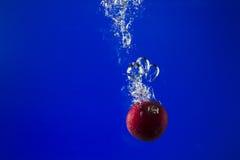 Apple στο νερό σε ένα μπλε υπόβαθρο Στοκ φωτογραφία με δικαίωμα ελεύθερης χρήσης
