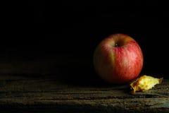 Apple στο ξύλινο πιάτο με το ευμετάβλητα και σκοτεινά ύφος και το υπόβαθρο Στοκ Εικόνες