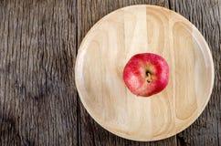 Apple στο ξύλινο πιάτο στο ξύλινο πάτωμα Στοκ εικόνα με δικαίωμα ελεύθερης χρήσης