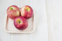 Apple στο ξύλινο πιάτο στο ξύλινο υπόβαθρο Στοκ Εικόνες