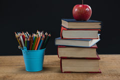 Apple στο σωρό βιβλίων με τα μολύβια χρώματος στον πίνακα Στοκ Εικόνα