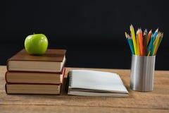 Apple στο σωρό βιβλίων με τα μολύβια χρώματος στον πίνακα Στοκ Φωτογραφίες