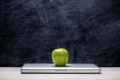 Apple στο lap-top στον πίνακα μπροστά από τον πίνακα κιμωλίας Στοκ εικόνα με δικαίωμα ελεύθερης χρήσης