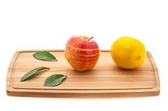 Apple φρέσκια και juicy με τα πράσινα φύλλα και το λεμόνι σε έναν τέμνοντα πίνακα φιαγμένο από ξύλο Στοκ εικόνα με δικαίωμα ελεύθερης χρήσης