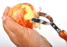 Apple. Removing of apple skin by blade Royalty Free Stock Image