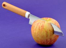 Apple. A knife cutting apple deeply Stock Photography
