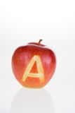 Apple with an A. Single apple with an A cut in to the front royalty free stock photography