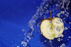 Apple. In a spray of water on a blue background Stock Photo