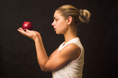 With apple. Lonely girl carrying red apple over black background Royalty Free Stock Image