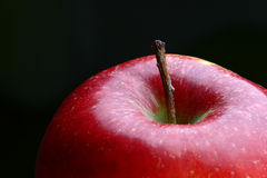 Apple. Closeup of a bright and fresh apple, with vivid tones of red, focus on the stem stock photos