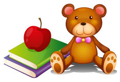 An apple above the books and a huggable bear Royalty Free Stock Image