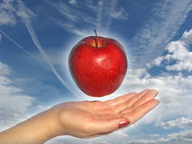 Apple above a hand - 2. Apple above a hand on a sky background Royalty Free Stock Images