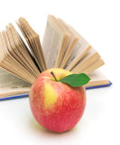Apple against an open book on white close-up Stock Photography