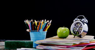 Apple and alarm clock on book stack with school supplies stock video footage