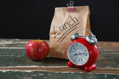 Apple, alarm clock and lunch bag on wooden table Stock Photo
