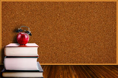 Apple Alarm Clock on Stack of Books and Corkboard Background Stock Photo