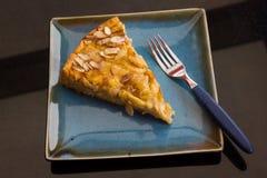 Apple almond kuchen cake dessert. Top view of tasty apple almond kuchen cake and fork on blue square plate. Restaurant delicatessen dessert, eat, German stock image