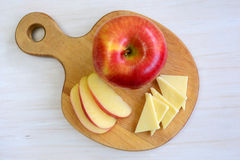 Apple on apple shaped board. Beautiful honeycrisp apple on unique apple shaped cutting board on rustic white background Stock Photos