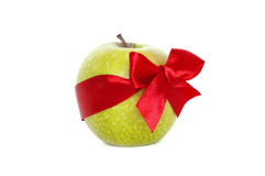 Apple as a gift. Fresh green apple with a red bow on a white background Royalty Free Stock Image