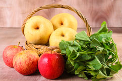 Apple and Asiatic in basket on wood background Royalty Free Stock Images