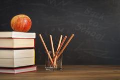 Apple auf Büchern mit Bleistiften und leerer Tafel - zurück zu Schule Lizenzfreie Stockbilder