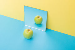 Apple auf blauer Tabelle über gelbem Hintergrund nahe Spiegel Stockbild