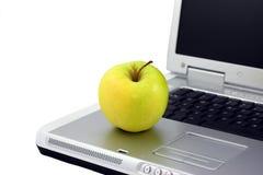 Apple auf einem Schoss-Spitzencomputer Stockfotos