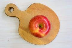Apple auf geformtem Brett des Apfels Stockbilder