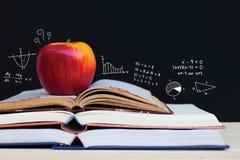 Apple auf Stapel offenen Büchern mit Bildung kritzelt Stockbilder