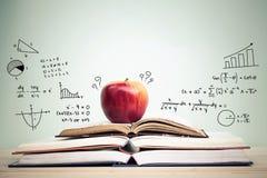 Apple auf Stapel offenen Büchern mit Bildung kritzelt Stockbild