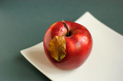 Apple with autumn leaves. Red apple with autumn leaves on a white plate Royalty Free Stock Images